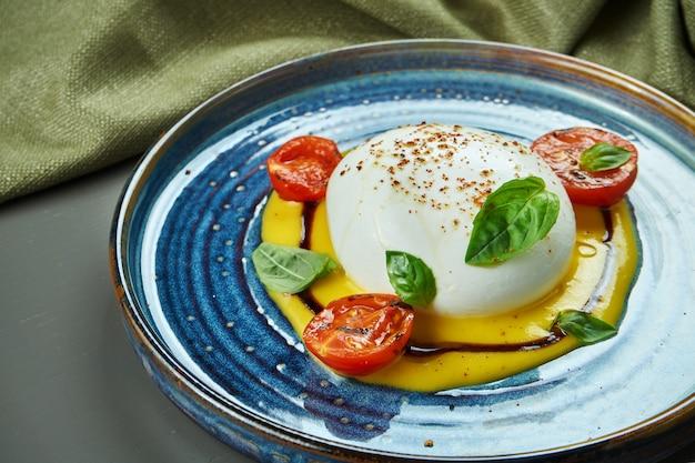 Аппетитный итальянский сыр буррата с моцареллой с персиковым кремом на синюю тарелку на деревянном столе. ресторан класса люкс еда. закройте, скопируйте пространство
