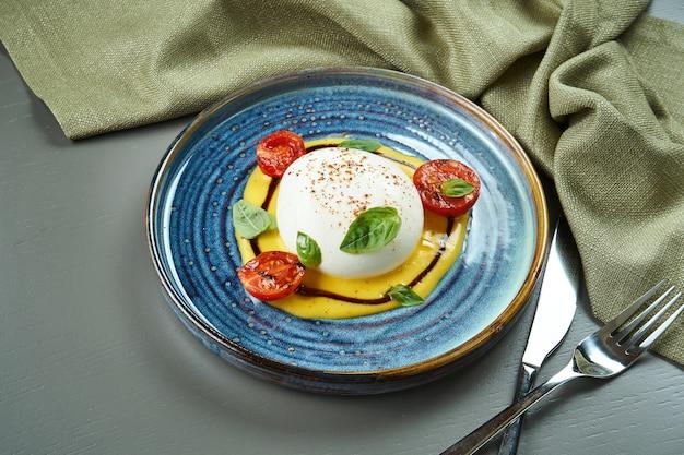 Аппетитный итальянский сыр буррата с моцареллой с персиковым кремом на синюю тарелку на деревянном столе. ресторан класса люкс еда. закрыть