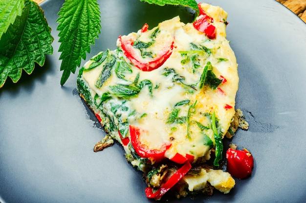 新鮮なハーブとイラクサを使った食欲をそそるイタリアンオムレツ。イタリア料理。健康的な食事