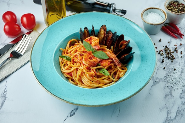 Appetizing italian pasta with tiger prawns, tomato sauce, chilean mussels in a blue plate on a marble surface