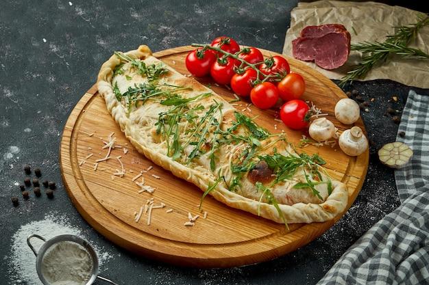 黒いテーブルの上の木の板の上に材料を含む組成物のさまざまな詰め物で食欲をそそるイタリアのピザカルゾーネ。上面図