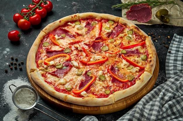 Аппетитная итальянская пицца с сыром, болгарским перцем, ветчиной, маринованными огурцами и красным соусом в композиции с ингредиентами на черном столе