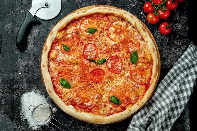 チーズ、トマト、バジル、レッドソースを使った食欲をそそるイタリアンピザを、黒いテーブルに材料を入れたコンポジションで。マルゲリータ