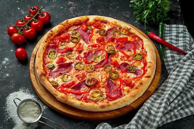Аппетитная итальянская пицца с ветчиной, сыром, перцем халапеньо, помидорами и болгарским перцем в композиции с ингредиентами на черном столе