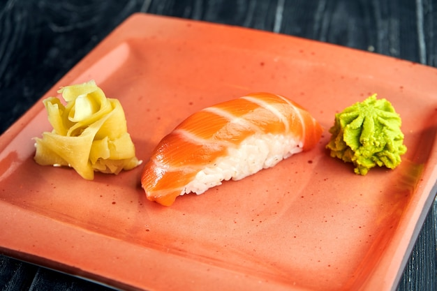 Appetizing japanese nigiri with fresh salmon and unagi sauce, served in a plate with ginger and wasabi on a black wooden surface