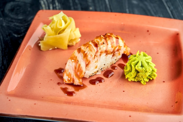 Appetizing japanese nigiri with smoked salmon and unagi sauce, served in a plate with ginger and wasabi on a black wooden surface