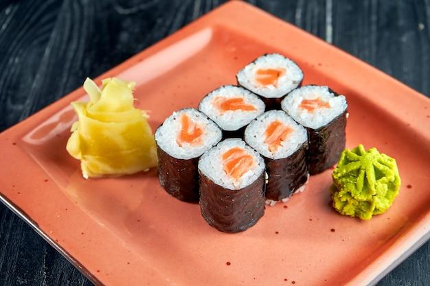 Аппетитные японские суши - маки с лососем, поданные в тарелке с имбирем и васаби на поверхности из черного дерева. японская кухня