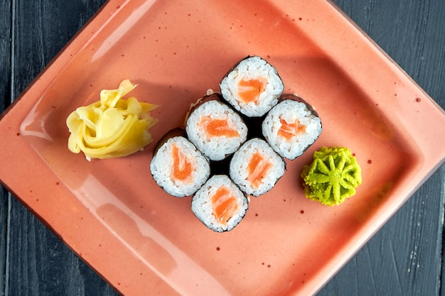 Appetizing japanese sushi - maki with salmon served in a plate with ginger and wasabi on a black wood surface. japanese cuisine