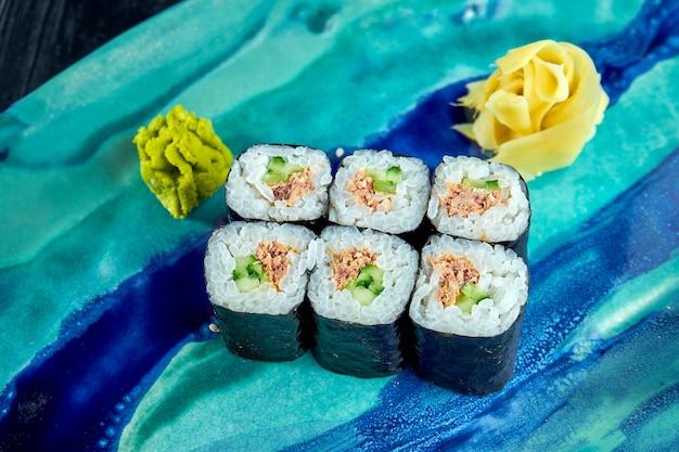 Аппетитные японские суши - маки с тунцом, поданные в тарелке с имбирем и васаби на поверхности из черного дерева. японская кухня