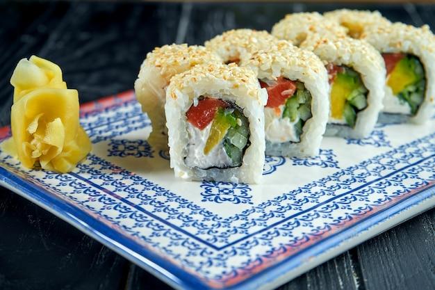 Аппетитный японский суши-ролл в кунжуте с лососем, авокадо и сливочным сыром в синей тарелке на черной деревянной поверхности. японская кухня. ролл филадельфия с кунжутом