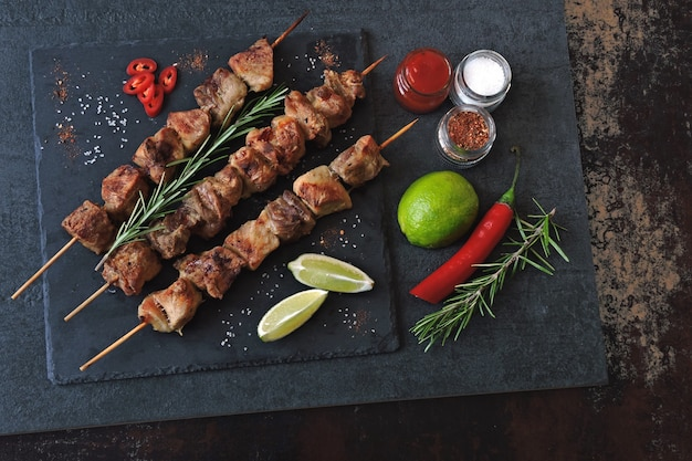 Appetizing kebab with spices, chili and lime. fragrant pork skewers on a stone board.