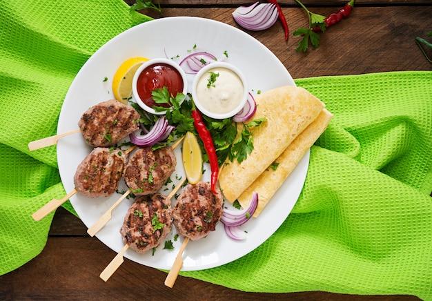 白いプレートにソースとトルティーヤタコスと食欲をそそるコフタケバブ(ミートボール)