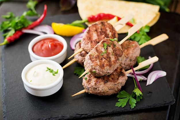 黒いテーブルにソースとトルティーヤタコスと食欲をそそるコフタケバブ(ミートボール)