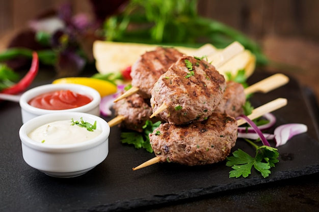 Appetizing kofta kebab (meatballs) with sauce and tortillas tacos on black table