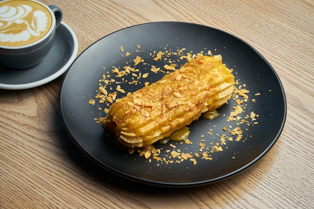 Appetizing and large eclair with glaze of mango on top and fir cream inside on a black plate. sweets and dessert for coffee and tea.