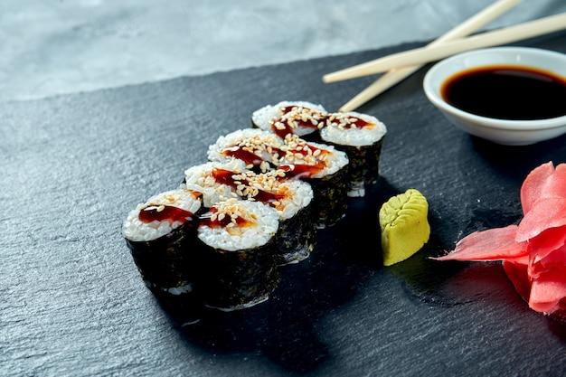 Аппетитные маки суши с угрем на черной грифельной доске