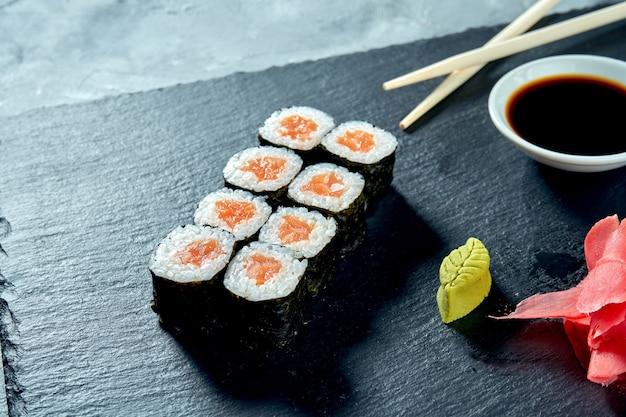 Аппетитные маки суши с лососем на черной грифельной доске