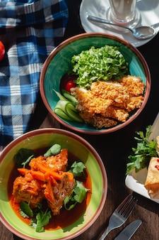 소스 (고기와 야채), 당근, 고수를 곁들인 식욕을 돋우는 고기 굴 라시, 아름다운 환경에서 테이블에 햇볕이 잘 드는 조명