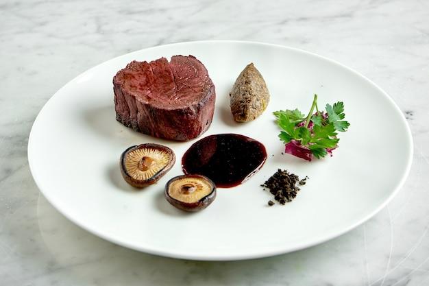 きのことベリーソースを添えた食欲をそそるミディアムレアのビーフステーキ。大理石のテーブルの白いプレートでお召し上がりいただけます。レストランの食べ物