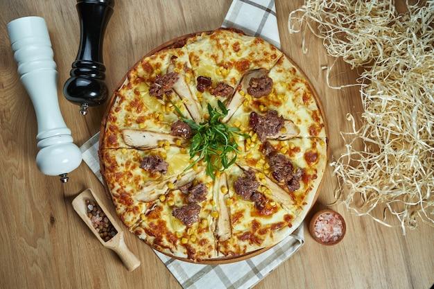 成分入りの組成の木製トレイに溶けたチーズ、チキン、トウモロコシ、ソフトビーフで食欲をそそるメキシコのピザ。上面図。食品フラットレイ