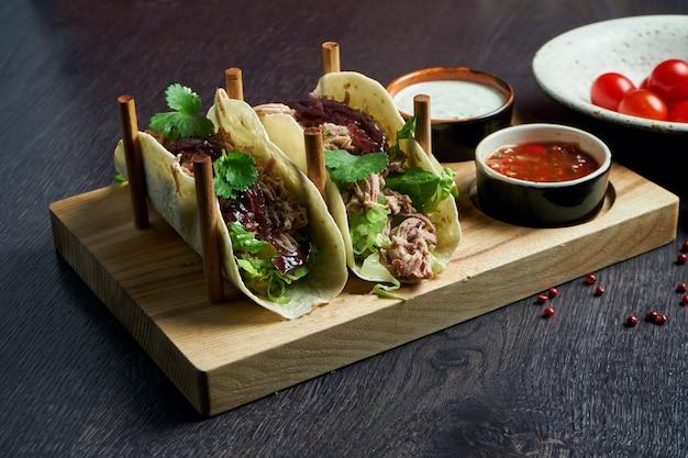 Аппетитные мексиканские тако с говядиной, капустой, луком и петрушкой на специальных подставках. традиционная мексиканская кухня