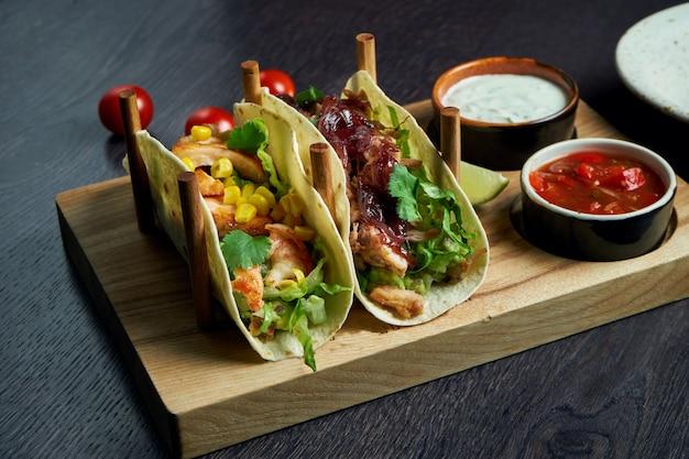 Аппетитные мексиканские тако с жареной курицей и тушеной говядиной, капустой, луком и петрушкой на специальных подставках. традиционная мексиканская кухня
