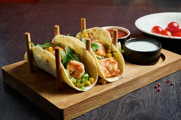 Аппетитные мексиканские тако с лососем и креветками, капустой, луком и петрушкой на специальных подставках. традиционная мексиканская кухня