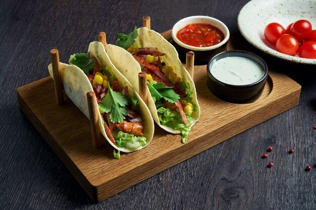 Аппетитные мексиканские тако с пряным салями, чоризо, капустой, луком и петрушкой на специальных подставках. традиционная мексиканская кухня