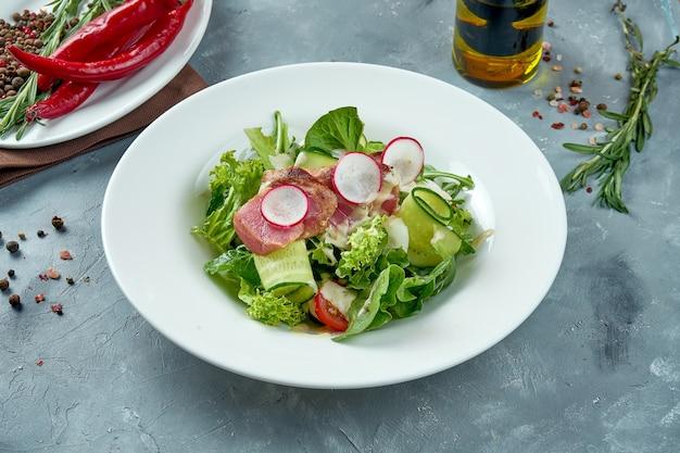 Appetizing nicoise salad with fresh tuna, radish, cucumber in a white plate