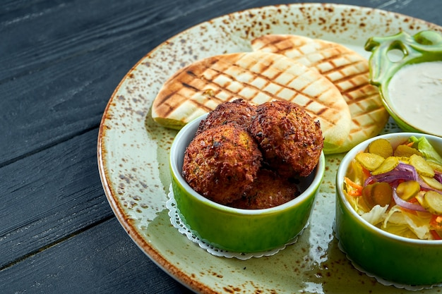 A appetizing oriental dish, falafel with pita bread, served with white sauce and pickles in a green plate against a dark, woody surface. vegetarian food