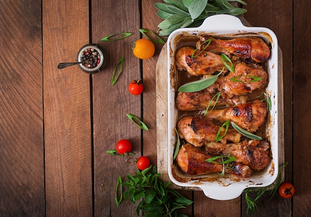 Appetizing oven baked golden chicken drumsticks in a baking dish  table. top view