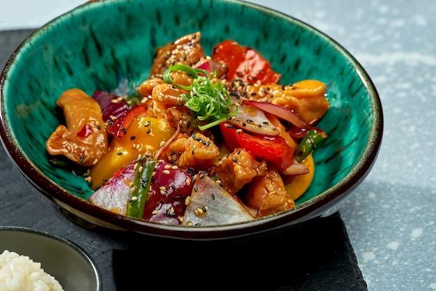 Аппетитное паназиатское блюдо - куриный вок в кисло-сладком соусе с болгарским перцем, луком, семенами кунжута и рисовым гарниром в синей миске на сером фоне