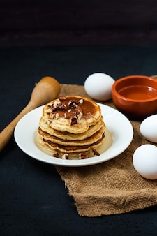 Appetizing pancakes with honey and nuts on a dark table with eggs and a bowl of honey menu , restaurant recipe  . served in