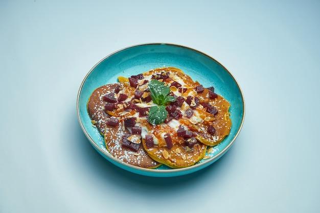 ジャム、サワークリーム、灰色の表面に分離された青い皿にカボチャと食欲をそそるパンケーキ。おいしい朝食料理