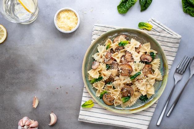灰色のコンクリート背景にキノコ、ほうれん草、チーズの食欲をそそるパスタ。健康食品のコンセプト。水平方向の画像。コピースペース。