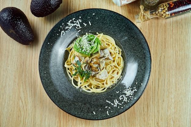 木製のテーブルの黒い皿にポルチーニ茸、アボカド、パルメザンチーズの食欲をそそるパスタ。イタリア料理。トップビューフラット横たわっていた食品。