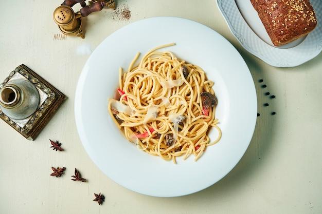 木製のテーブルの白いプレートプレートでパルメザンチーズと野菜の食欲をそそるパスタ。イタリア料理。トップビューフラット横たわっていた食品。