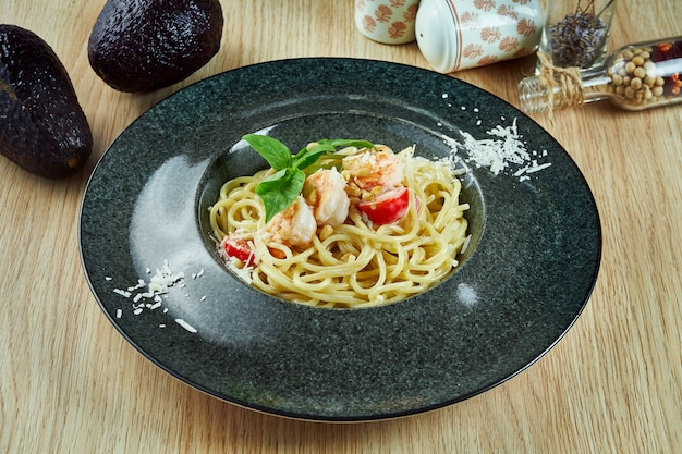 Appetizing pasta with with shrimps, cherry tomato, basil and parmesan in a black plate on a wooden table. italian cuisine. top view flat lay food.
