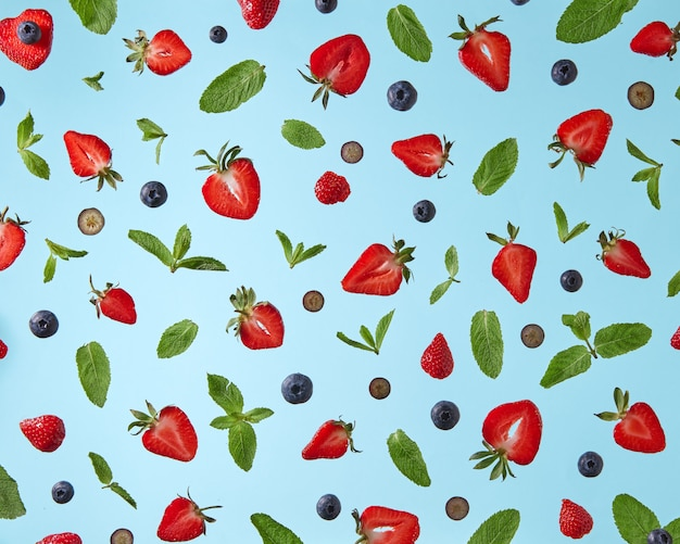 Appetizing pattern of blueberry strawberries and green mint leaves