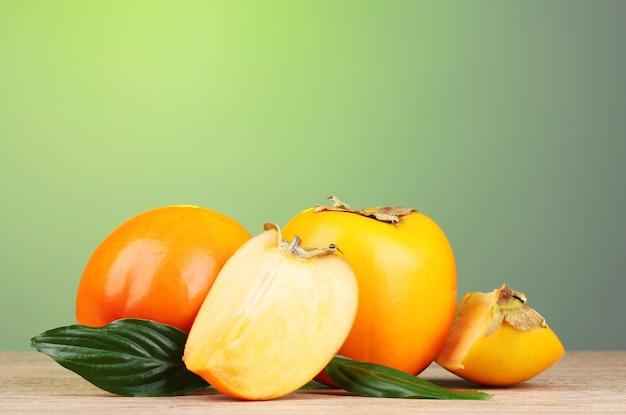 緑の表面の木製テーブルに食欲をそそる柿