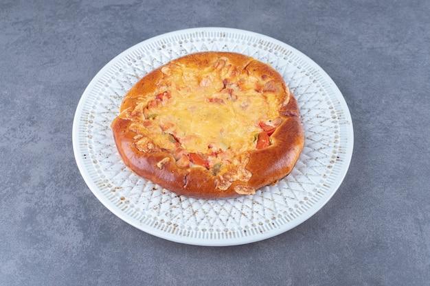 Pizza appetitosa su un piatto sulla tavola di marmo.