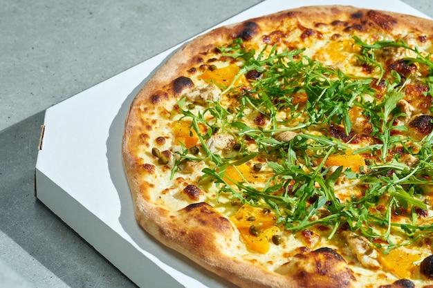 クリーミーなソース、チキン、イエロートマト、ケーパーを使った食欲をそそるピザ。ぱりっとした側面。ハードライト。灰色の表面。