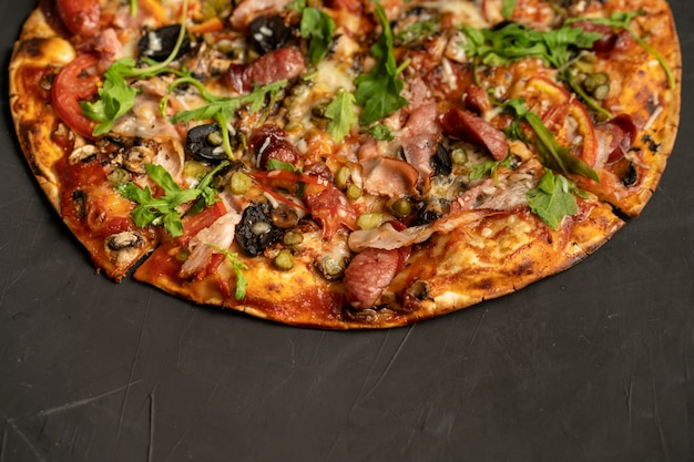 Appetizing pizza with smoked sausages bacon meat tomato cheese arugula on black dark . with copyspace