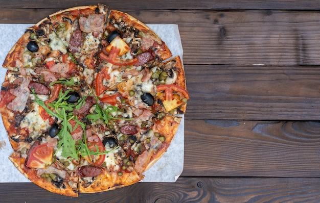 Appetizing pizza with smoked sausages bacon meat tomato cheese arugula cardboard boxes for delivery on black dark . with copyspace