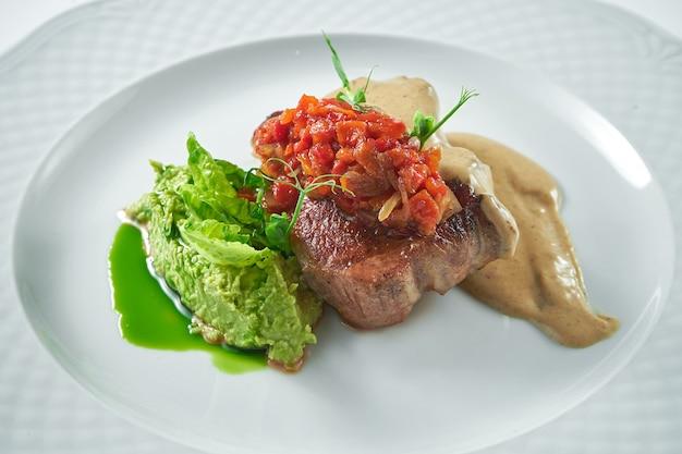 흰 접시에 토마토 살사, 버섯 소스, 으깬 완두콩을 곁들인 식욕을 돋우는 돼지 고기 스테이크. 클로즈업, 선택적 초점