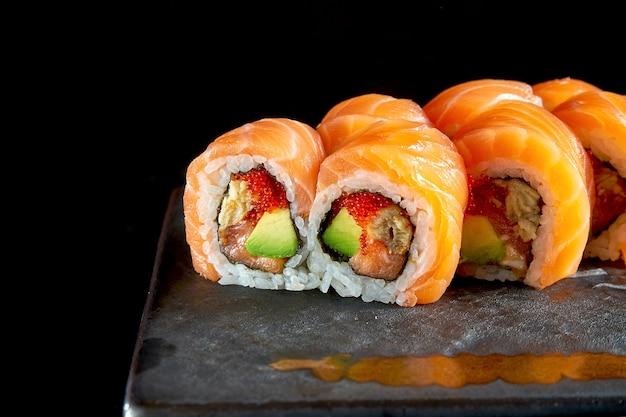 Аппетитный суши-ролл «красный дракон» с лососем, угрем, авокадо и икрой тобико, подается на керамической тарелке с имбирем и васаби.
