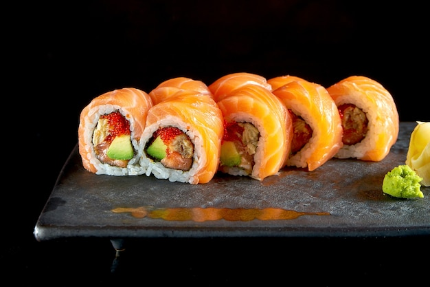 Appetizing red dragon sushi roll with salmon, eel, avocado and tobiko caviar, served on a ceramic plate with ginger and wasabi.