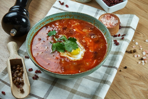 Appetizing red soup on meat broth with vegetables and quail egg. close up view. tasty food