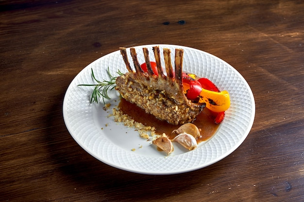 Appetizing roasted rack of lamb in nuts, with sauce and grilled vegetables, served in a white plate on a wooden surface