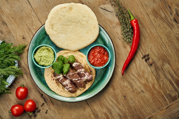 Appetizing rolls of lyulya kebab - cooked over a lamb minced meat with a side dish of hummus with pita and salsa on ceramic plate. vertical, wooden surface, eastern cuisine